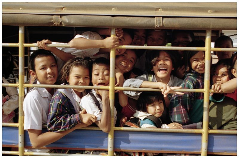 A songthaew (baht bus) loaded with students on the way home from school in Kantharalak