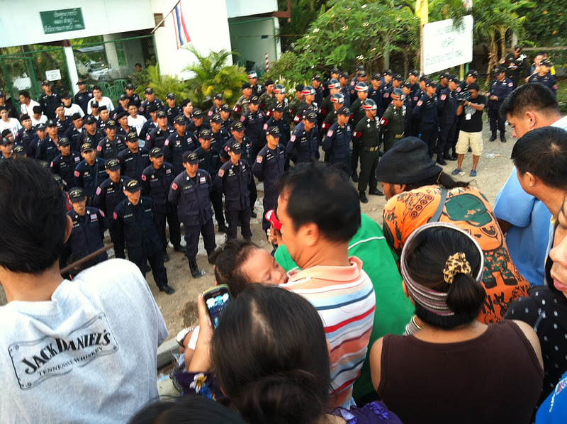 Onlookers watch Thai police and soldiers line up