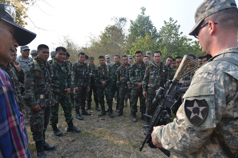 U.S. Army Staff Sgt. Andrew Renfroe, right, familiarizes Royal Thai Army counterparts with the M320 grenade launcher