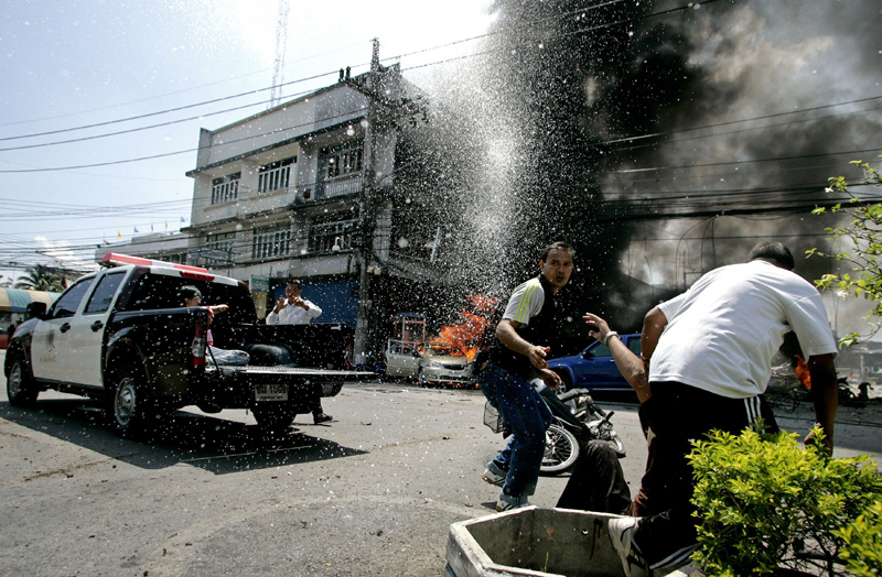 Thai policemen assist an injured person after a grenade bomb exploded outside a police station in Pattani